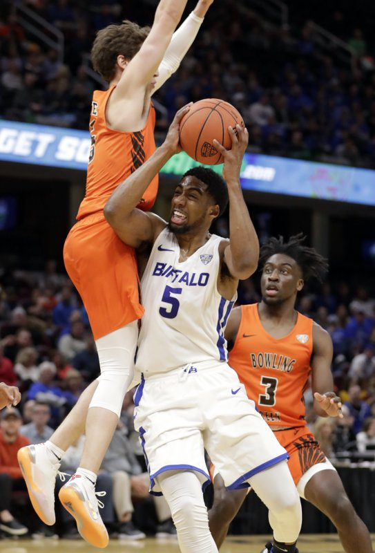 Buffalo's CJ Massinburg, right, drives against Bowling Green's Dylan Frye during the first half of an NCAA college basketball championship game of the Mid-American Conference men's tournament, Saturday, March 16, 2019, in Cleveland. (AP Photo/Tony Dejak)