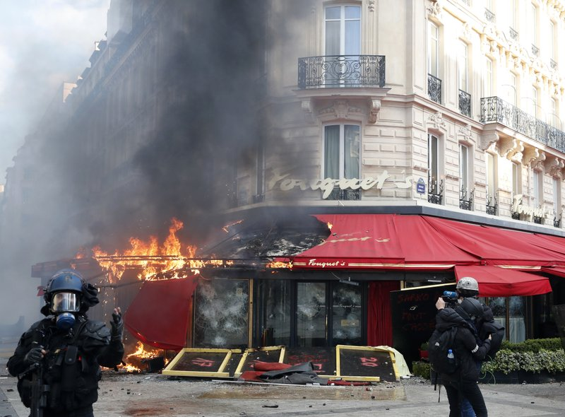 Paris famed restaurant Fouquet's burns on the Champs Elysees avenue during a yellow vests demonstration Saturday, March 16, 2019 in Paris. (AP Photo/Christophe Ena)