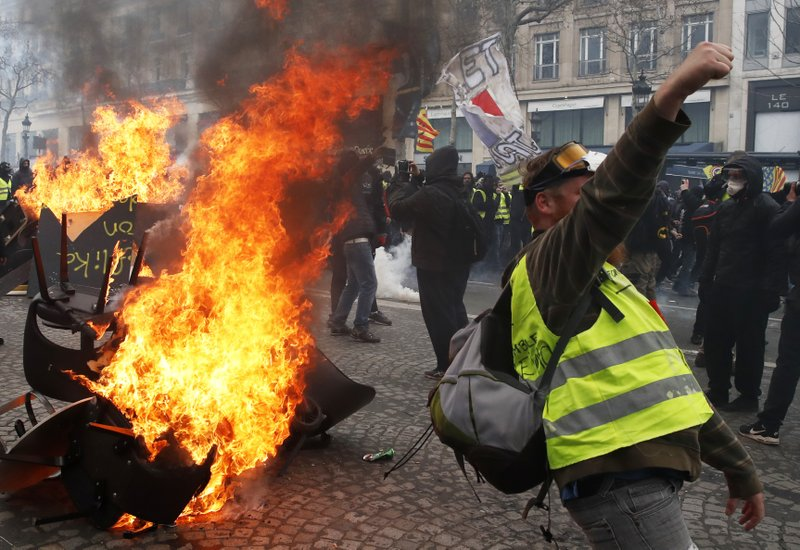 A protester shouts slogans in front of a barricade on fire during a yellow vests demonstration Saturday, March 16, 2019 in Paris. (AP Photo/Christophe Ena)
