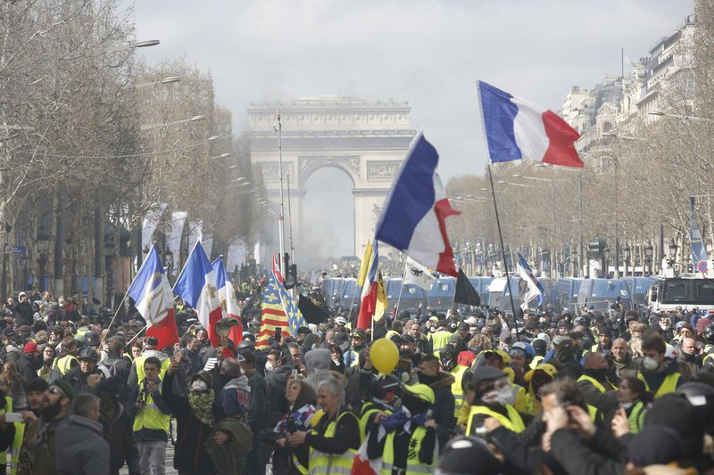 Yellow vests demonstrators invade the Champs Elysees avenue Saturday, March 16, 2019 in Paris. French yellow vest protesters clashed Saturday with riot police near the Arc de Triomphe as they kicked off their 18th straight weekend of demonstrations against President Emmanuel Macron. (AP Photo/Christophe Ena)