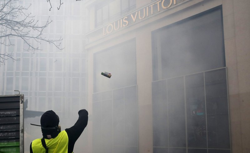A protester throws a device on the Louis Vuitton luxury shop on the Champs Elysees avenue, during a yellow vests demonstration Saturday, March 16, 2019 in Paris. (AP Photo/Christophe Ena)
