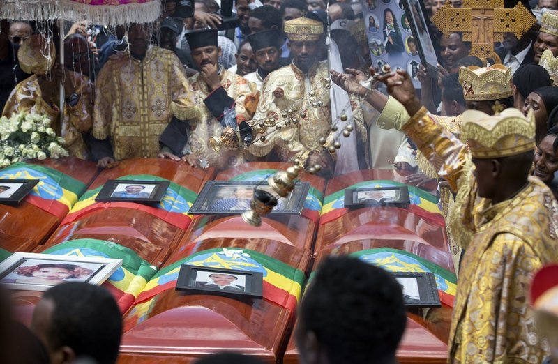 Priests swing incense over empty caskets draped with the national flag at a mass funeral at the Holy Trinity Cathedral in Addis Ababa, Ethiopia Sunday, March 17, 2019. (AP Photo/Mulugeta Ayene)