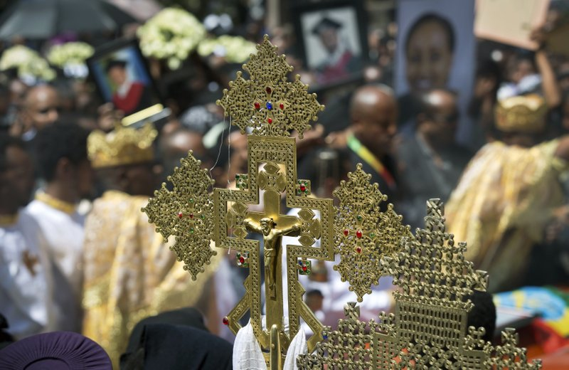 A crucifix is held by a priest at a mass funeral at the Holy Trinity Cathedral in Addis Ababa, Ethiopia Sunday, March 17, 2019. (AP Photo/Mulugeta Ayene)