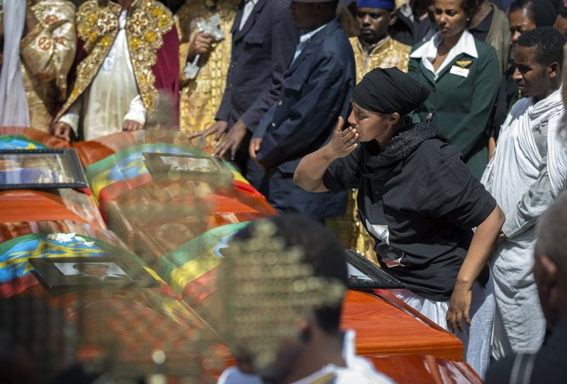 A relative blows a kiss towards empty caskets draped with the national flag at a mass funeral at the Holy Trinity Cathedral in Addis Ababa, Ethiopia Sunday, March 17, 2019. (AP Photo/Mulugeta Ayene)