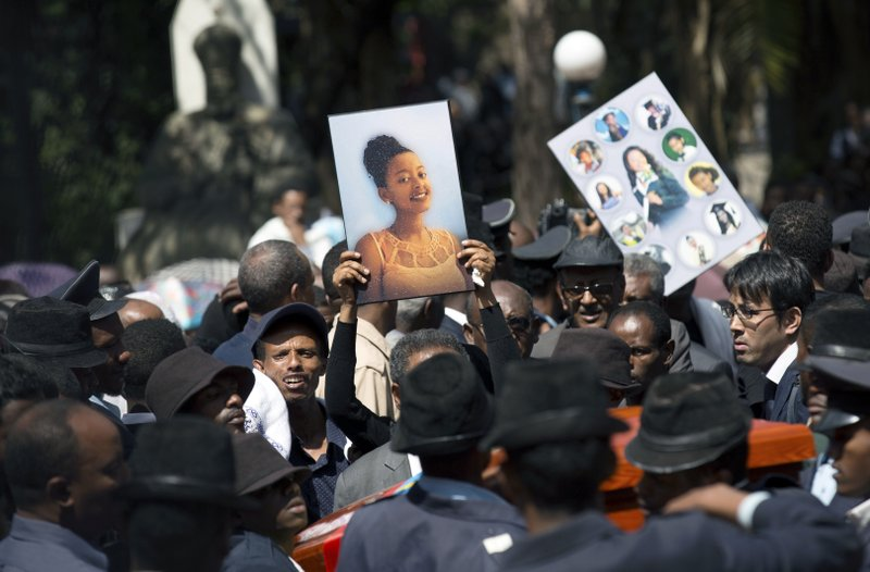 Relatives hold photographs of the victims at a mass funeral at the Holy Trinity Cathedral in Addis Ababa, Ethiopia Sunday, March 17, 2019. (AP Photo/Mulugeta Ayene)