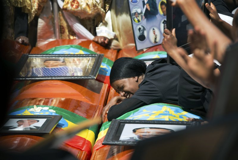 Relatives grieve next to empty caskets draped with the national flag at a mass funeral at the Holy Trinity Cathedral in Addis Ababa, Ethiopia Sunday, March 17, 2019. (AP Photo/Mulugeta Ayene)