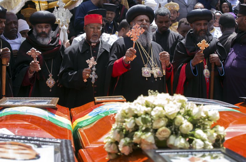 Church leaders pray next to empty caskets draped with the national flag at a mass funeral at the Holy Trinity Cathedral in Addis Ababa, Ethiopia Sunday, March 17, 2019. (AP Photo/Mulugeta Ayene)