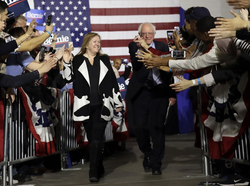 FILE - In this March 3, 2019, file photo, Sen. Bernie Sanders, I-Vt., right, and his wife Jane Sanders, greet supporters as they arrive arrive for a campaign event at Navy Pier in Chicago. (AP Photo/Nam Y. Huh, File)