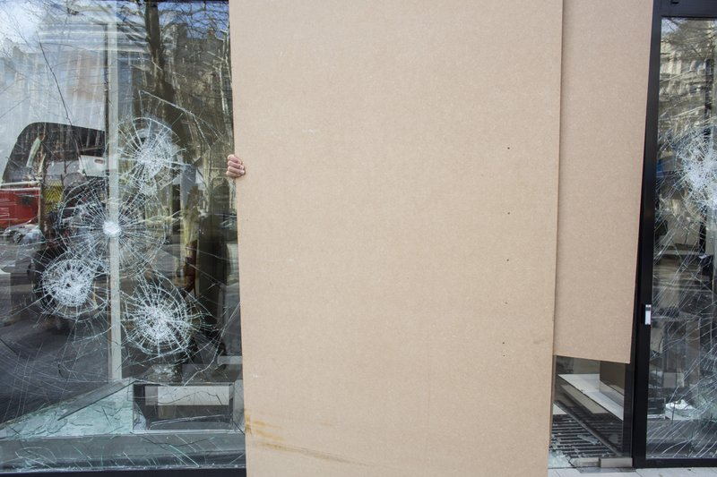 A worker sets up protection on the smashed windows of a store the day after it was vandalized during the 18th straight weekend of demonstrations by the yellow vests, in Paris, France, Sunday, March 17, 2019. (AP Photo/Rafael Yaghobzadeh)
