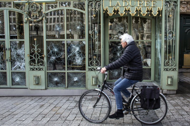 A cyclist rides past the smashed windows of the famed tea salon Laduree on the Champs Elysees the day after it was vandalized during the 18th straight weekend of demonstrations by the yellow vests, in Paris, France, Sunday, March 17, 2019. (AP Photo/Rafael Yaghobzadeh)