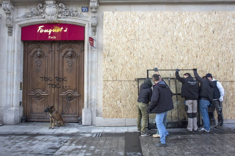 Workers set up protection on shop windows of the famed Champs Elysees restaurant Fouquet's, the day after it was vandalized and set on fire during the 18th straight weekend of demonstrations by the yellow vests, in Paris, France, Sunday, March 17, 2019. (AP Photo/Rafael Yaghobzadeh)