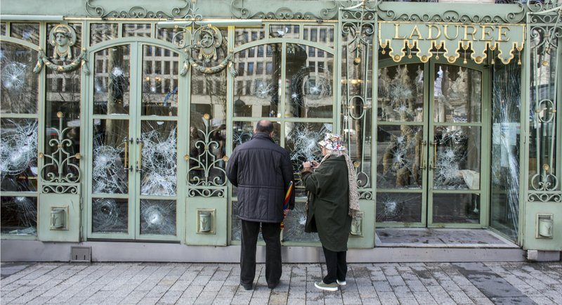 Bystanders take snapshots of the smashed windows of the famed tea salon Laduree on the Champs Elysees the day after it was vandalized during the 18th straight weekend of demonstrations by the yellow vests, in Paris, France, Sunday, March 17, 2019. (AP Photo/Rafael Yaghobzadeh)