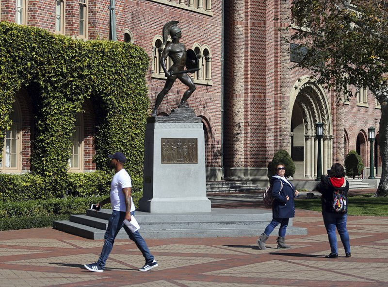 FILE - In this March 12, 2019 file photo, people pose for photos in front of the iconic Tommy Trojan statue on the campus of the University of Southern California in Los Angeles. (AP Photo/Reed Saxon, File)