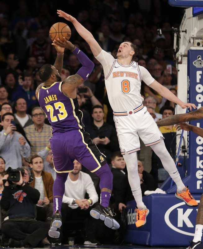 New York Knicks' Mario Hezonja (8), right, blocks what could have been the winning shot by Los Angeles Lakers' LeBron James, left, during the second half of an NBA basketball game, Sunday, March 17, 2019, in New York. (AP Photo/Seth Wenig)