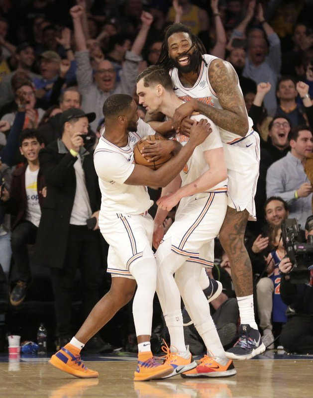 New York Knicks' DeAndre Jordan, right, and Emmanuel Mudiay, left, celebrate with Mario Hezonja, center, after he blocked the last shot of an NBA basketball game during the second half Sunday, March 17, 2019, in New York. (AP Photo/Seth Wenig)