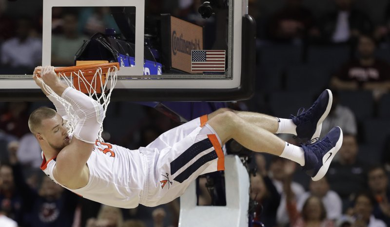 Virginia's Jack Salt (33) hangs from the rim after a dunk against North Carolina State during the second half of an NCAA college basketball game in the Atlantic Coast Conference tournament in Charlotte, N. (AP Photo/Chuck Burton)