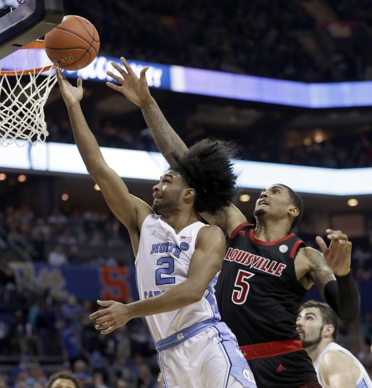 North Carolina's Coby White (2) drives past Louisville's Malik Williams (5) during the second half of an NCAA college basketball game in the Atlantic Coast Conference tournament in Charlotte, N. (AP Photo/Nell Redmond)