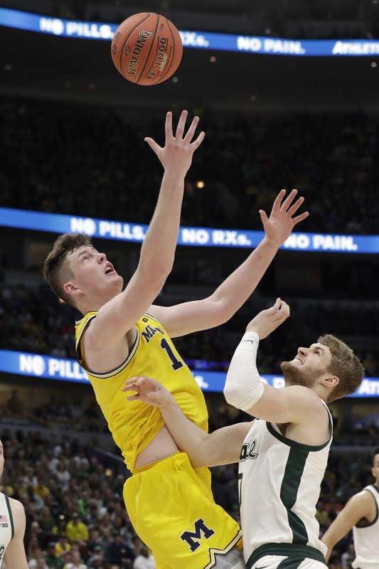 Michigan's Jon Teske, left, goes up for a rebound against Michigan State's Kyle Ahrens during the first half of an NCAA college basketball championship game in the Big Ten Conference tournament, Sunday, March 17, 2019, in Chicago. (AP Photo/Nam Y. Huh)