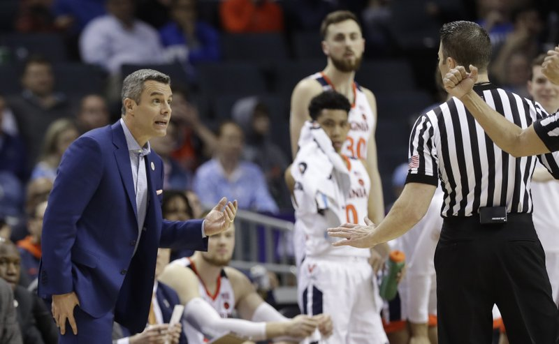 Virginia coach Tony Bennett discusses a call with an official during the second half of an NCAA college basketball game against Florida State in the Atlantic Coast Conference tournament in Charlotte, N. (AP Photo/Chuck Burton)