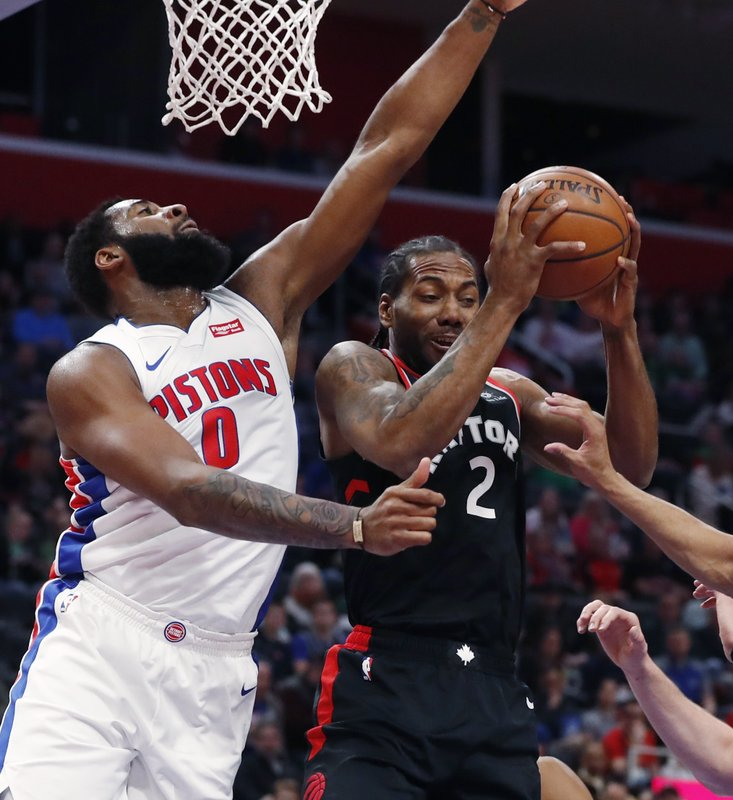 Toronto Raptors forward Kawhi Leonard (2) pulls down a rebound as Detroit Pistons center Andre Drummond (0) defends during the first half of an NBA basketball game Sunday, March 17, 2019, in Detroit. (AP Photo/Carlos Osorio)