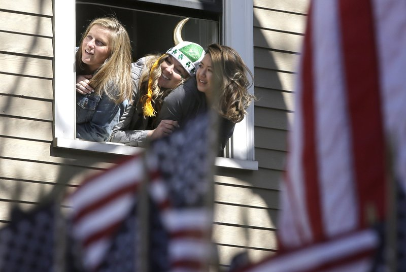 Spectators watch from a window during the annual St. Patrick's Day parade, Sunday, March 17, 2019, in Boston's South Boston neighborhood. (AP Photo/Steven Senne)