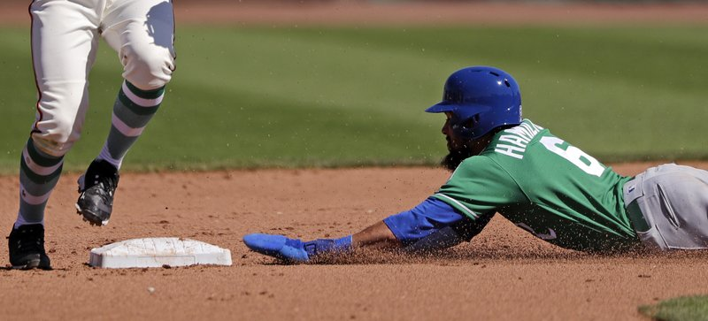 Kansas City Royals' Billy Hamilton slides safely into second base for a stolen base in the fifth inning of a spring training baseball game against the San Francisco Giants Sunday, March 17, 2019, in Scottsdale, Ariz. (AP Photo/Elaine Thompson)