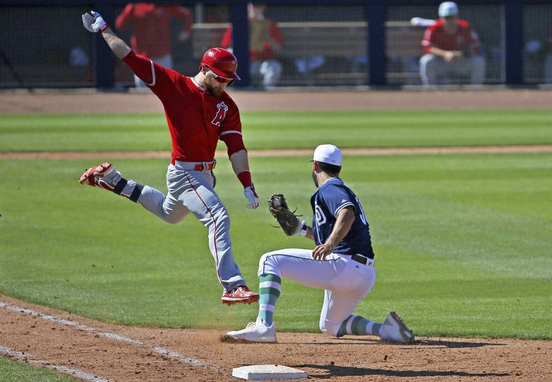 San Diego Padres first baseman Eric Hosmer, right, tags out a leaping Los Angeles Angels' Jonathan Lucroy, left, during the fifth inning of a spring training baseball game Sunday, March 17, 2019, in Peoria, Ariz. (AP Photo/Ross D. Franklin)