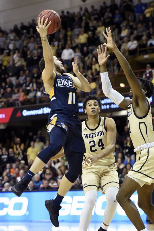 UNC-Greensboro guard Demetrius Troy (11) drives the ball to the basket against Wofford forward Keve Aluma (24) and forward Chevez Goodwin (1) in the second half of an NCAA college basketball game for the Southern Conference tournament championship, Monday, March 11, 2019, in Asheville, N. (AP Photo/Kathy Kmonicek)