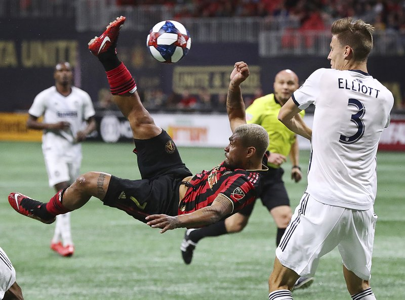 Atlanta United forward Josef Martinez makes a bicycle kick next to Philadelphia Union defender Jack Elliott that was blocked by goalkeeper Andre Blake during the second half of an MLS soccer match that ended in a 1-1 draw, Sunday, March 17, 2019, in Atlanta. (Curtis Compton/Atlanta Journal-Constitution via AP)