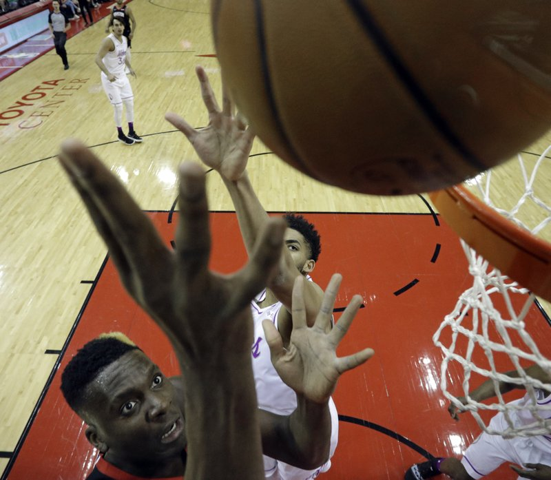 Houston Rockets' Clint Capela, left, shoots as Minnesota Timberwolves' Karl-Anthony Towns defends during the first half of an NBA basketball game Sunday, March 17, 2019, in Houston. (AP Photo/David J. Phillip)