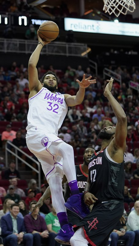 Minnesota Timberwolves' Karl-Anthony Towns (32) goes up for a shot as Houston Rockets' Nene Hilario (42) defends during the first half of an NBA basketball game Sunday, March 17, 2019, in Houston. (AP Photo/David J. Phillip)