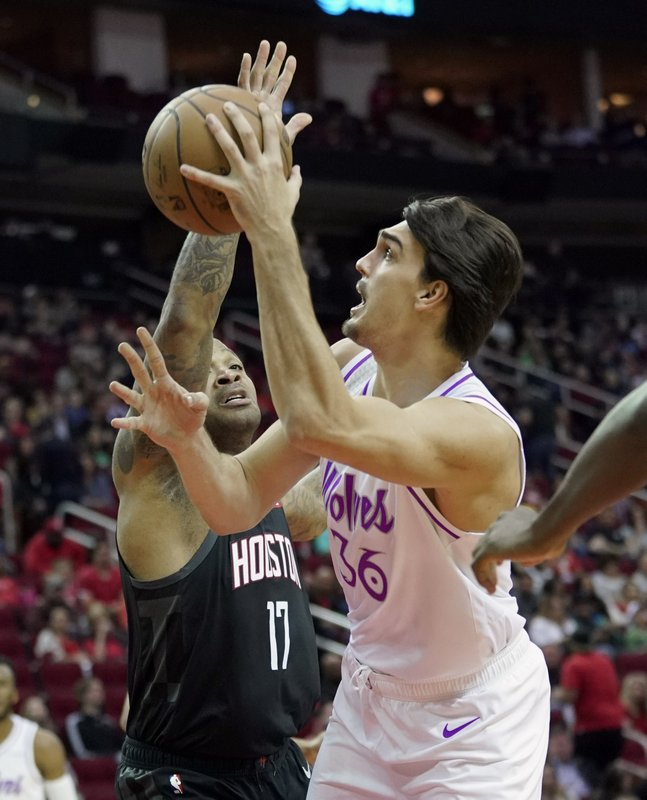 Minnesota Timberwolves' Dario Saric (36) shoots as Houston Rockets' PJ Tucker (17) defends during the first half of an NBA basketball game Sunday, March 17, 2019, in Houston. (AP Photo/David J. Phillip)