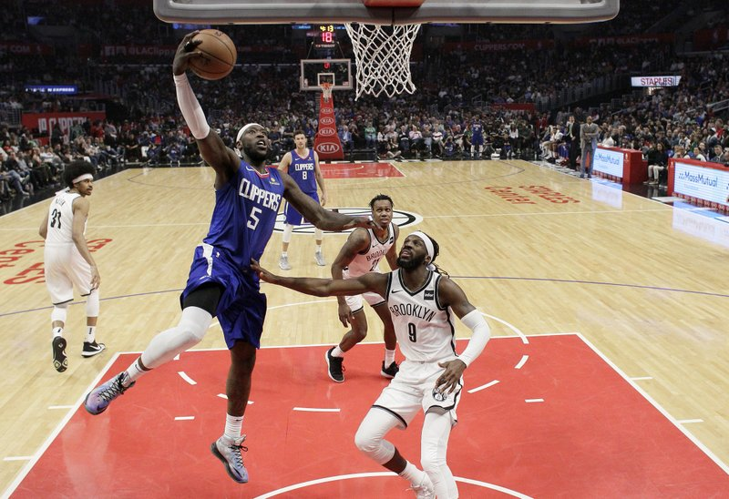 Los Angeles Clippers' Montrezl Harrell (5) drives to the basket past Brooklyn Nets' DeMarre Carroll (9) during the first half of an NBA basketball game Sunday, March 17, 2019, in Los Angeles. (AP Photo/Marcio Jose Sanchez)