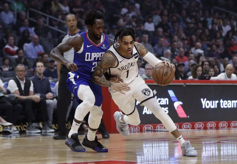 Brooklyn Nets' D'Angelo Russell, right, drives around Los Angeles Clippers' Patrick Beverley during the first half of an NBA basketball game Sunday, March 17, 2019, in Los Angeles. (AP Photo/Marcio Jose Sanchez)