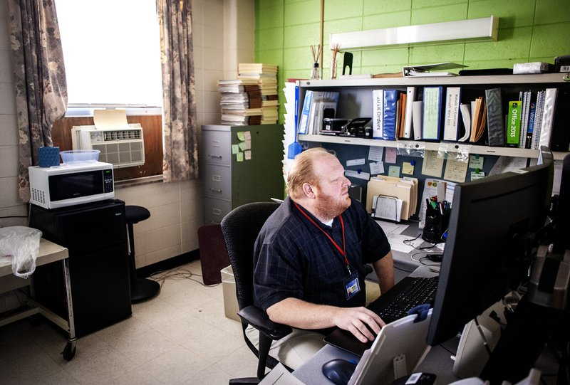 Michael Southern, a user support employee, sits at his desk at the Rock County Health Care Center in Janesville, Wis. (Angela Major/The Janesville Gazette via AP)