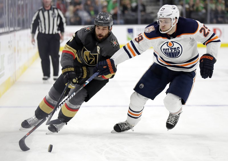 Vegas Golden Knights defenseman Deryk Engelland (5) skates with the puck as Edmonton Oilers left wing Leon Draisaitl defends during the second period of an NHL hockey game Sunday, March 17, 2019, in Las Vegas. (AP Photo/Isaac Brekken)