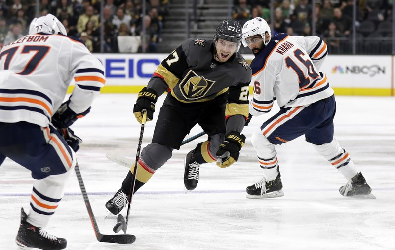 Vegas Golden Knights defenseman Shea Theodore (27) skates with the puck through Edmonton Oilers defenders during the second period of an NHL hockey game Sunday, March 17, 2019, in Las Vegas. (AP Photo/Isaac Brekken)
