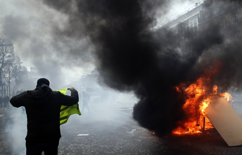 Yellow vests protesters set a burricade afire on the Champs Elysees avenue Saturday, March 16, 2019 in Paris. (AP Photo/Christophe Ena)