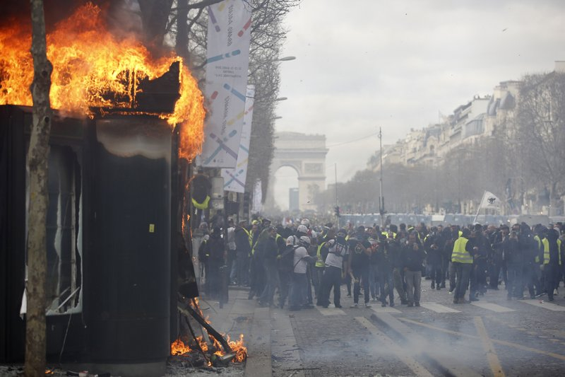 A news stands burns during a yellow vests demonstration on the Champs Elysees avenue Saturday, March 16, 2019 in Paris. (AP Photo/Christophe Ena)