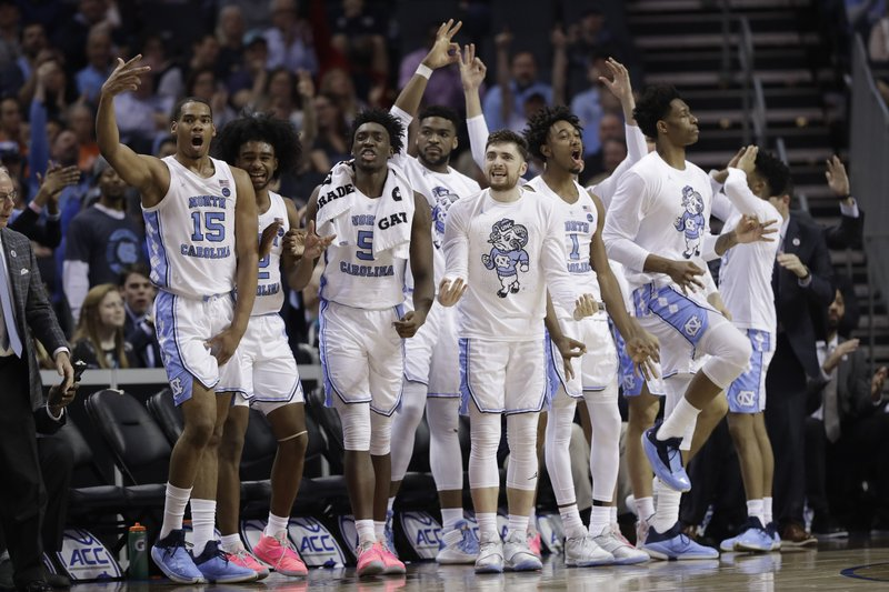 North Carolina players celebrate a teammate's basket against Louisville during the second half of an NCAA college basketball game in the Atlantic Coast Conference tournament in Charlotte, N. (AP Photo/Chuck Burton)