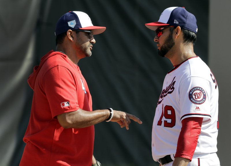 FILE - In this Feb. 16, 2019, file photo, Washington Nationals manager Dave Martinez, left, talks with pitcher Anibal Sanchez during spring training baseball practice, in West Palm Beach, Fla. (AP Photo/Jeff Roberson, File)