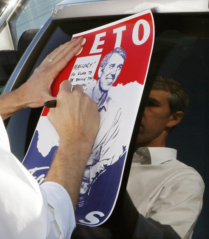 Former Texas congressman and Democratic presidential candidate Beto O'Rourke signs a placard after a visit to the Michigan Regional Council of Carpenters, Monday, March 18, 2019 in Ferndale, Mich. (AP Photo/Carlos Osorio)
