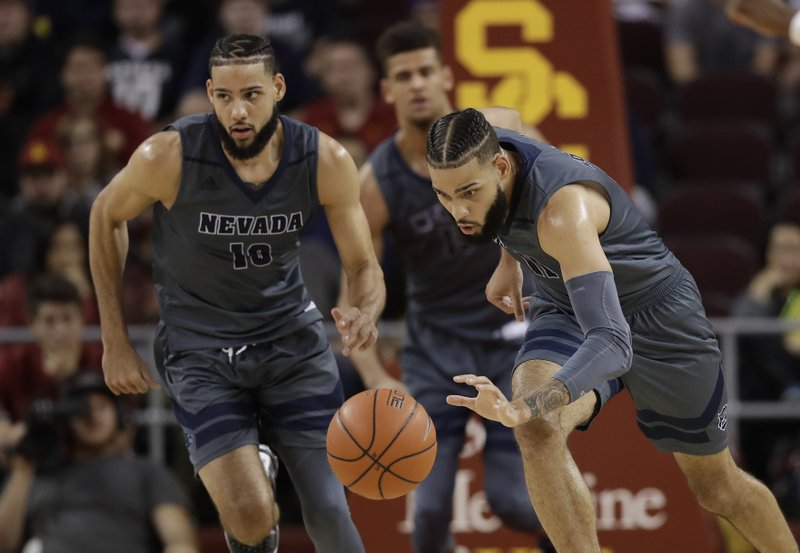 FILE - In this Dec. 1, 2018, file photo, Nevada forward Cody Martin, right, dribbles downcourt as his twin brother Caleb Martin, left, trails during the second half of an NCAA college basketball game against Southern California in Los Angeles. (AP Photo/Marcio Jose Sanchez, File)
