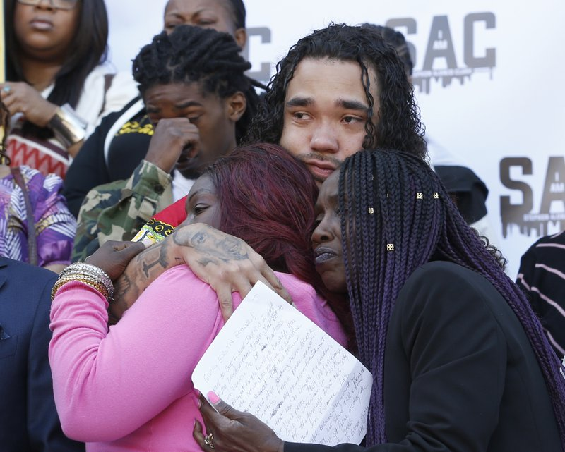Trayvon Wiseman, center, a cousin of police shooting victim Stephon Clark, hugs Clark's mother, SeQuette Clark, left, and grandmother, Sequitta Thompson, right, during a news conference at the Capitol on vMonday, March 18, 2019, in Sacramento, Calif. (AP Photo/Rich Pedroncelli)