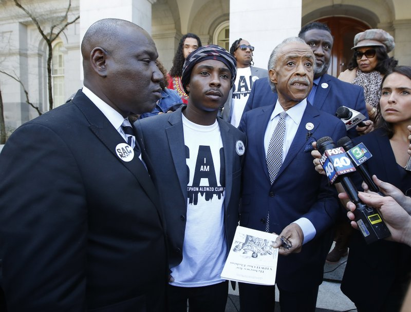The Rev. Al Sharpton, second from right, accompanied by Stevante Clark, center, the brother of police shooting victim Stephon Clark, and attorney Benjamin Crump, left, talks to reporter after a news conference Monday, March 18, 2019, in Sacramento, Calif. (AP Photo/Rich Pedroncelli)