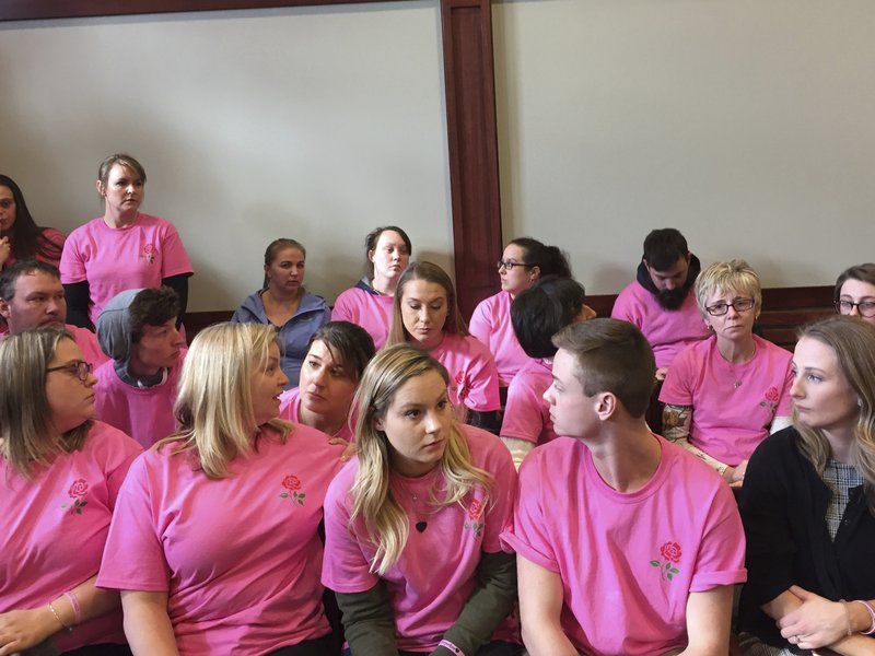 Harper Rose Briar's parents, Marissa Colburn, center, and Blake Briar, right, are joined by over 30 people wearing pink T-Shirts that read