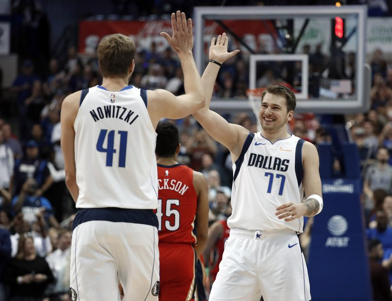 Dallas Mavericks' Dirk Nowitzki (41) and Luka Doncic (77) celebrate after Nowitzki scored a basket against the New Orleans Pelicans in the first half of an NBA basketball game in Dallas, Monday, March 18, 2019. (AP Photo/Tony Gutierrez)