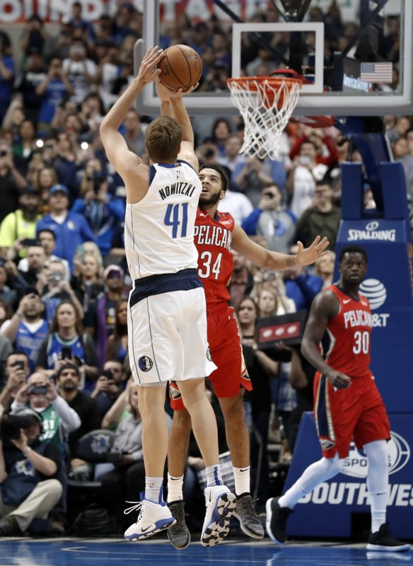 Dallas Mavericks forward Dirk Nowitzki (41) shoots as New Orleans Pelicans' Kenrich Williams (3) defends and Pelicans' Julius Randle (30) and Anthony Davis (23) watch in the first half of an NBA basketball game in Dallas, Monday, March 18, 2019. (AP Photo/Tony Gutierrez)