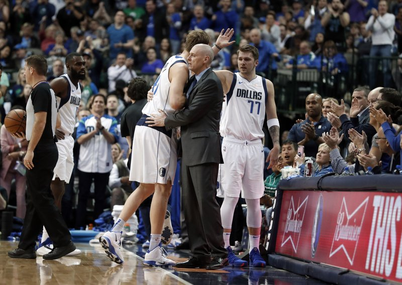 Dallas Mavericks forward Dirk Nowitzki (41) gets a hug from head coach Rick Carlisle as Luka Doncic (77) waits to greet Nowitzki at the bench after Nowitkzi sunk a basket in the first half of an NBA basketball game against the New Orleans Pelicans in Dallas, Monday, March 18, 2019. (AP Photo/Tony Gutierrez)