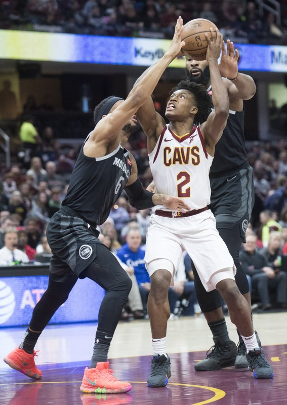 Cleveland Cavaliers guard Collin Sexton drives to the basket between Detroit Pistons guard Bruce Brown and center Andre Drummond in the first half of an NBA basketball game, Monday, March 18, 2019, in Cleveland. (AP Photo/Ken Blaze)